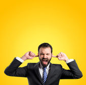 Business man covering her ears over yellow background  — Foto de Stock