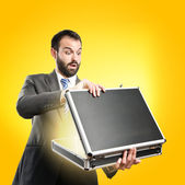 Young businessman open his briefcase over yellow background — Foto de Stock