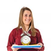 Student holding a clock over white background   — Stock Photo