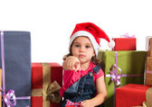 Blonde christmas kid around several presents pointing to the fro — Stock Photo