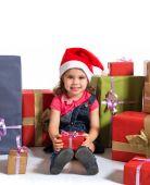 Blonde christmas kid around several presents — Stock Photo