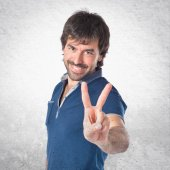 Man doing victory gesture over white background — Stock Photo