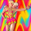 Dance party scene with two blond 3d fashion and beauty models posing together against a colorful abstract background. — Stock fotografie #62925173