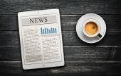 News article on digital tablet and coffee cup — Stock Photo