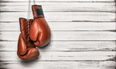 Boxing gloves hanging on wooden wall — Stock Photo