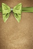 Green bow on texture of paper packaging — Stock Photo