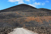 A road on volcanic landscape at  Lanzarote Island, Canary Island — Stock Photo
