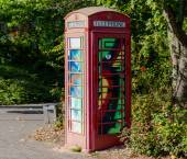 Painted old red phone booth, phone box, painted in different col — Stock Photo