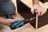 Woodworker Assembling Furniture made of chipboard using a cordless screwdriver. — Stock Photo