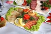 Fish delicacies on laid table — Stock Photo