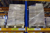 Pallets with boxes stand on a shelf goods warehouse. — Stock Photo