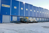 Modern Warehouse outside,  trucks are unloaded at loading docks, evening. — Foto de Stock