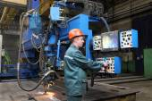 Working operator controls welding robot, standing at control panel — Stock Photo