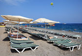 Sunbeds and parasols on  beach near resort of Kemer. — Foto Stock