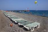 Sunbeds on pebbled beach of Mediterranean resort. — Stock Photo