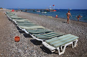 Deck chairs on the pebble beach of Mediterranean resort.  — Stock Photo