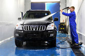 Young man washing his car with compression water — Stock Photo
