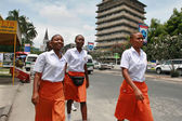 Four black African women in uniform, orange skirts and white shirt. — Stock Photo