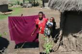 Maasai village, dark-skinned woman holds a child. — Stock Photo