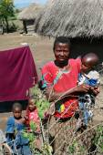 Maasai village, the African family standing near huts. — Stock Photo
