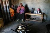 Internal view of maasai hut, black woman and children  indoors.  — Stock Photo