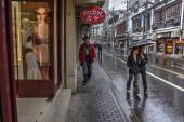Passers flow along wet pavementwalked past store on city street. — Stock Photo
