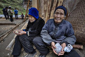 Two older farmer Asians, rural women, sitting near peasant house — Stock Photo