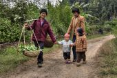 Villagers in China, women with children, are on country road. — Stock Photo