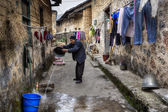 Asian elderly villager pours water from bucket on narrow street. — Stock Photo