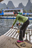 Asian girl ferryman crosses river on raft with motor, China. — Stock Photo