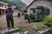 Chinese peasants in village street, next to three-wheeled green — Stock Photo
