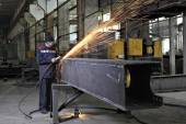 Metalworkers polishing welds metal structures, producing fountain of sparks. — Stock Photo