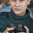 Male paparazzi photographer holding a digital photo camera, indoor shot with particular focus on hands and camera — Stock Photo #69574691