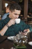 Smiling man using laptop in the cafe — Stock Photo