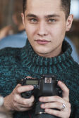 Male paparazzi photographer holding a digital photo camera, indoor shot with particular focus on hands and camera — Stock Photo