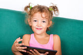 Smiling little girl with tablet — Stock Photo