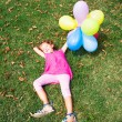 Funny little girl lying on the grass in the park — Stock Photo #66070575