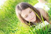 Girl reading on the lawn — Stock Photo