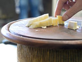 Hand grasping cubes of cheese on a wooden cutting board ready fo — Stock Photo