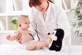 Smiling doctor pediatrician playing and enjoy with baby patient — Stock Photo