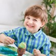 Adorable smiling happy child boy painting on paper and  easter e — Stock Photo #66886995