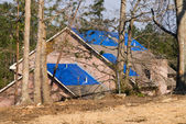 Tornado damaged house with a blue tarpaulin on the roof — Stockfoto
