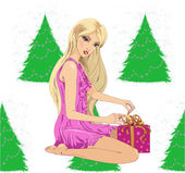 Pretty woman near christmas tree unwrapping present — Stock Vector