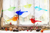 Interior window with glass birds and nuts — Stock Photo