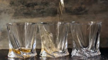 Pouring whiskey in three glasses — Stock Video