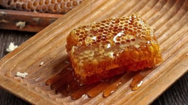 Honeycombs with pouring honey from wooden honey dipper — Stock Video