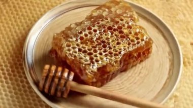 Rotating ceramic plate with honeycomb and wooden honey dipper — Stock Video