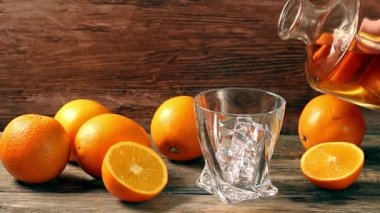Pouring whiskey from bottle to glass over gray background with orange — Stock Video