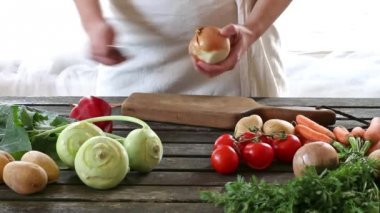 Woman slice vegetables. Woman slice onion on wooden table. Rustic style. — Stock Video