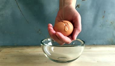 Breaking eggs in a glass bowl, slow motion — Стоковое видео